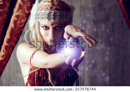 Magnificent fortune teller holding crystal ball. Magic.  - stock photo