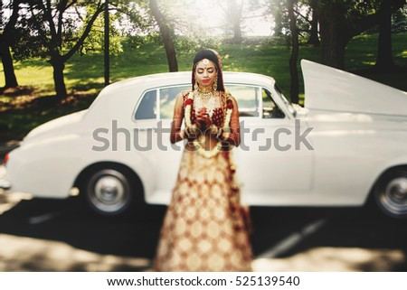 Magnificent Hindu bride prays standing in the rays of sun before a white retro car