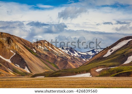 Magnificent Iceland in the summer. Valley National Park Landmannalaugar. On the gentle slopes of the mountains are snow fields and glaciers - stock photo