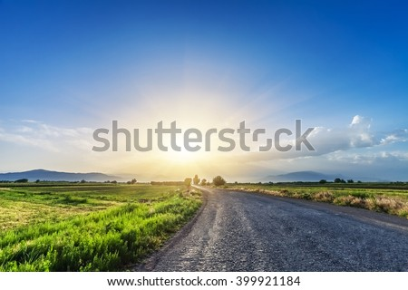magnificent landscape of road on meadow on background of beautiful sunset sky with clouds - stock photo