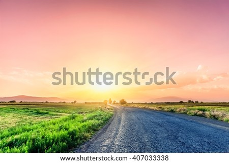 magnificent landscape of road on meadow on background of beautiful sunset sky with clouds. Exploring Armenia - stock photo