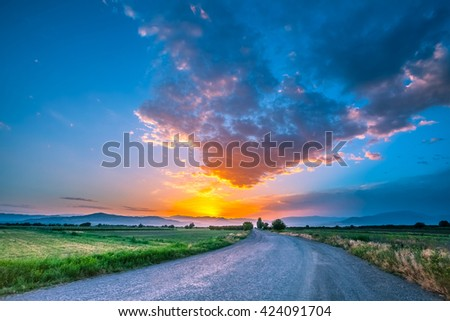 magnificent landscape of road on meadow on background of beautiful sunset sky with clouds