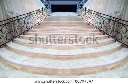 magnificent light marble staircase with ornate metal railings - stock photo