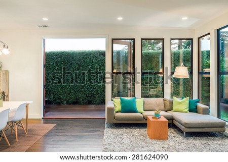 Magnificent living room in contemporary home at twilight with large windows surrounded by trees. Hardwood floor with hand-woven natural fine sisal rug in open space living room with couch.  - stock photo