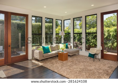 Magnificent living room in contemporary home with large windows and double french doors surrounded by trees. Hardwood floor with hand-woven natural fine sisal rug in with couch and bookshelf.  - stock photo