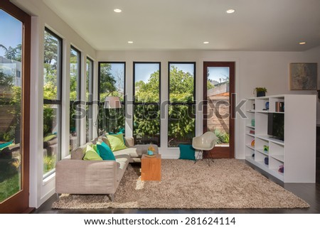 Magnificent living room in contemporary home with large windows surrounded by trees. Hardwood floor with hand-woven natural fine sisal rug in open space living room with couch and bookshelf.  - stock photo