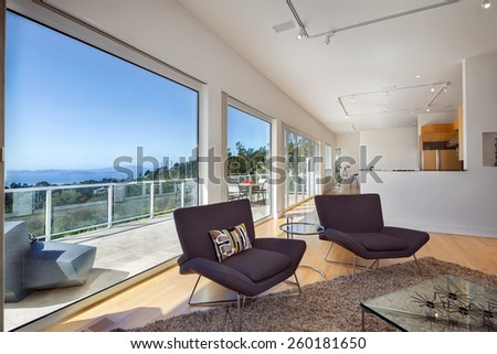 Magnificent living room in contemporary, modern home with large view window and balcony, terrace. Hardwood floor with hand-woven natural fine sisal rug, glass table, designer chairs in open space. - stock photo