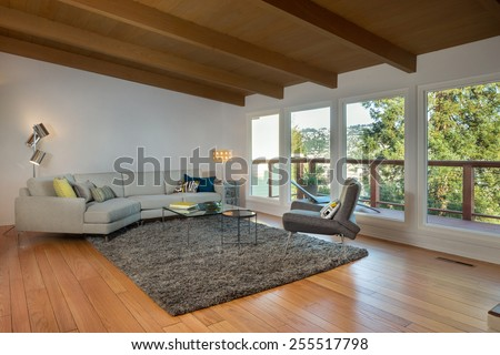 Magnificent mid century living room interior with designer couch and colorful pillows, lights, french sliding doors, hardwood floor, natural colored fine sisal rug, view window in open space concept. - stock photo