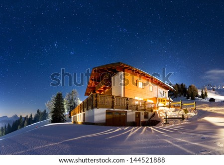 Magnificent panorama of a house on the mountain with a lot of stars at night - stock photo