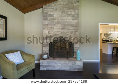 Magnificent stone framed fire place and olive green armchair within living room. - stock photo