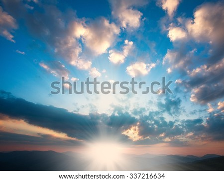 Magnificent sunrise over the mountains on the background of the cloudy sky - stock photo