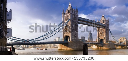 Magnificent Victorian Tower Bridge of London built in 1894 still stands as a symbol of the city. Converted brick warehouses and Thames beach and river. - stock photo