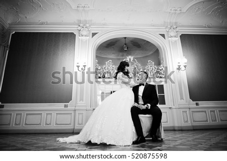 Magnificent wedding couple sitting on chair on royal room with many mirrors.