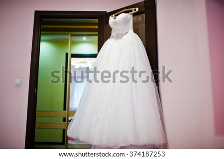 Magnificent wedding dress on hanger at pink room
