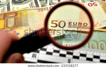 magnifier and a lot of banknotes lie on against white background