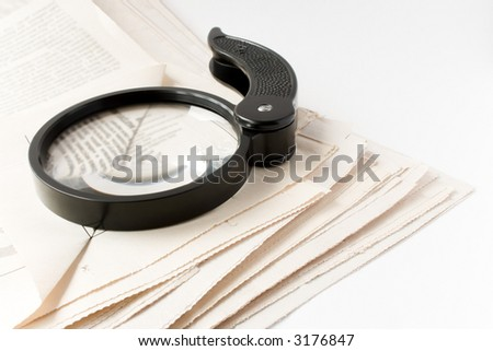 Magnifier and newspaper - stock photo