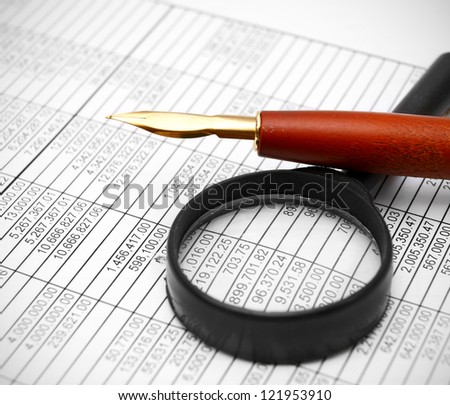 Magnifier and pen on documents. - stock photo