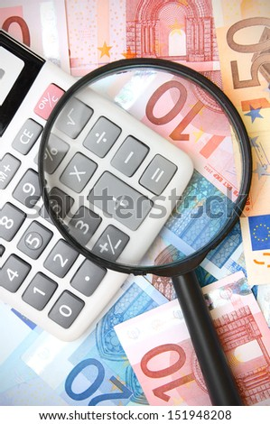 Magnifier and the calculator on money. - stock photo