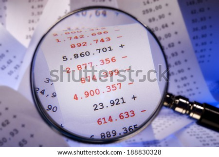 Magnifier focused red numbers on a billing - stock photo