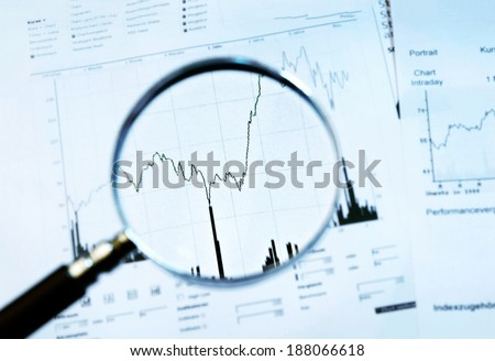 Magnifier focuses a chart with stock price - stock photo