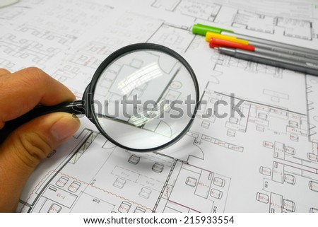 Magnifier glass and paper part of architectural project - stock photo