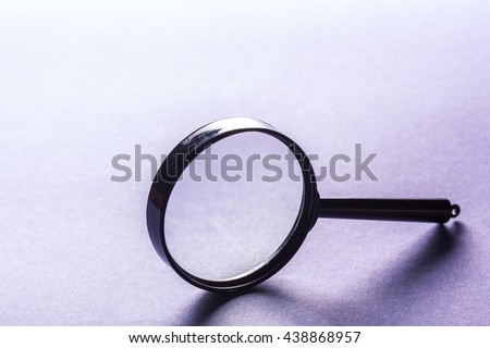 Magnifier on blue background close up