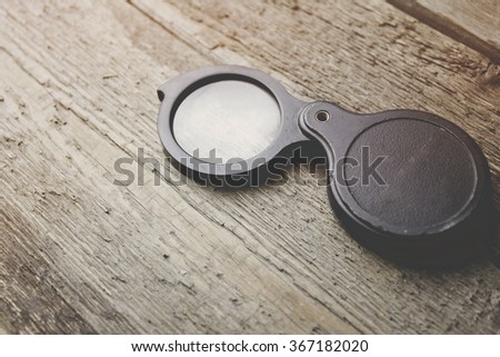 Magnifier on the wooden table - stock photo