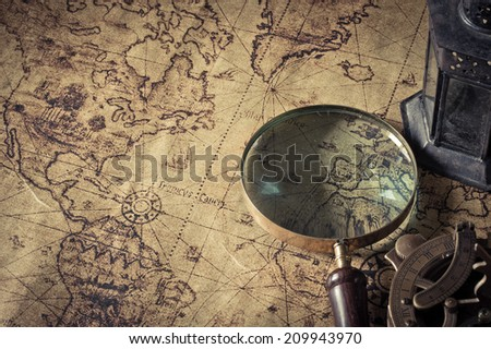Magnifier with lantern with compass on the  old map  ,picture style vintage - stock photo