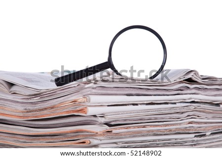 Magnify glass over a stack of newspaper to find fresh information (isolated on white) - stock photo