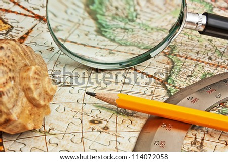 magnifying glass and a pencil on a map - stock photo