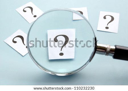 magnifying glass and a question mark on the paper - stock photo
