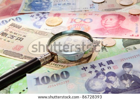 magnifying glass and Background of asian currency (include Korean Won, Taiwan dollar, Chinese Money yuan , Hong Kong Dollar, japanese Yen) - stock photo