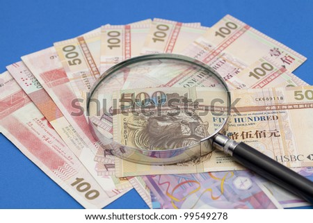 magnifying glass and dollars honkong - stock photo