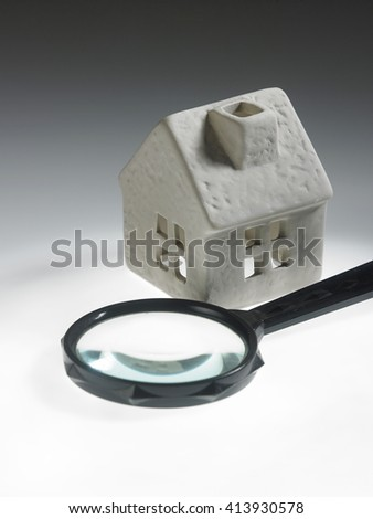 magnifying glass and house model isolated over white background - stock photo