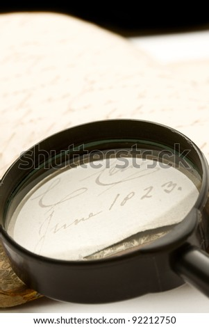 Magnifying glass and old book - stock photo