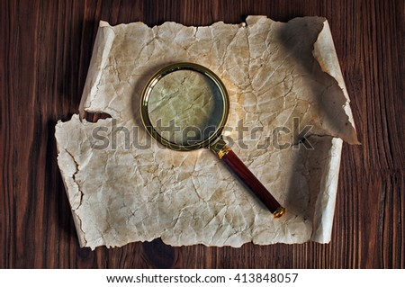 Magnifying glass and old parchment  on a wooden table