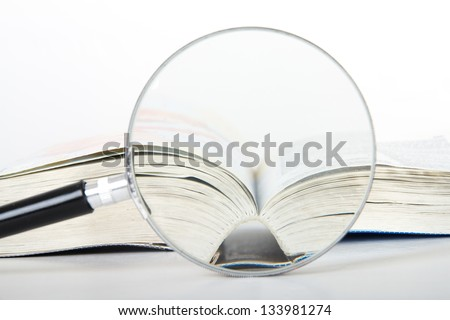 Magnifying glass and open dictionary book, isolated on white background. - stock photo