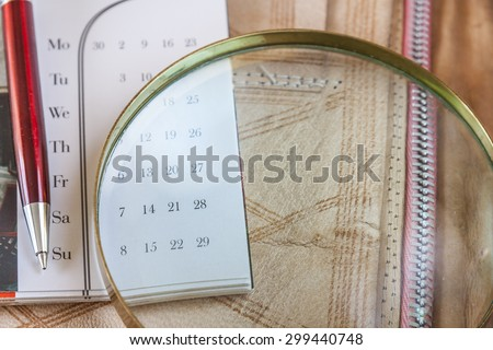 Magnifying Glass and Pen On Calendar - stock photo
