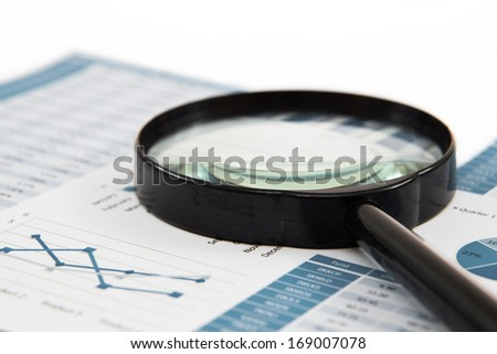 magnifying glass and pen over graph on table - stock photo