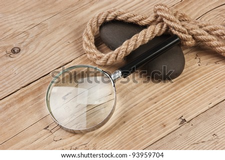 magnifying glass and rope on a wooden background