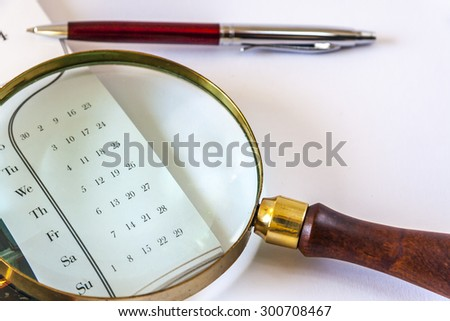 Magnifying Glass And The Pen Are Lying On The Calendar