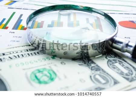 magnifying glass and US dollar on graph background