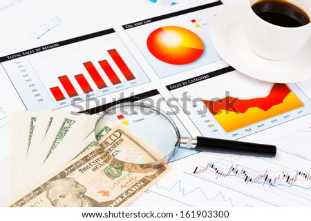 magnifying glass, bills, a cup of coffee, financial documents with charts and graphs, business still life