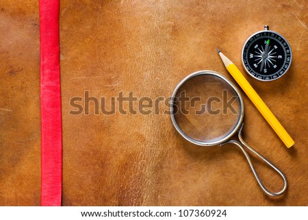 Magnifying glass, compass and pencil on old gunge leather background - stock photo