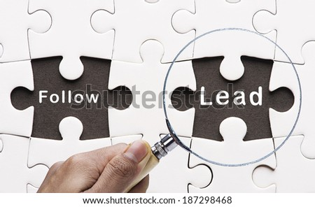 "Magnifying glass focusing missing puzzle peace ""Lead"" - stock photo"