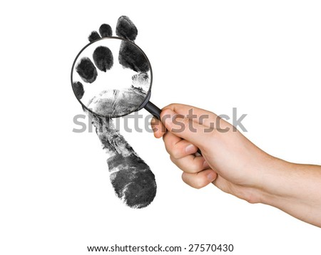 Magnifying glass in hand and foot printout isolated on white background - stock photo