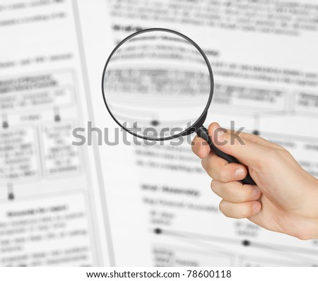 Magnifying glass in hand and text - business background - stock photo