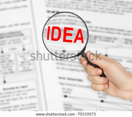 Magnifying glass in hand and word Idea - business background - stock photo
