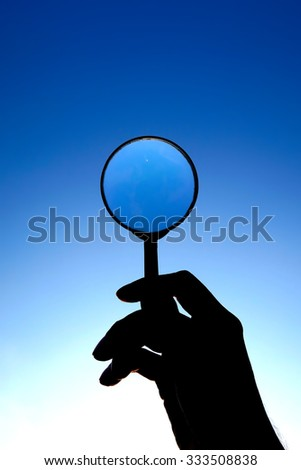 Magnifying Glass in the Hand on the Evening Sky Background closeup - stock photo