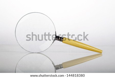Magnifying glass isolated on white background with shadow reflection and back lighting paper effect - stock photo